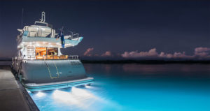 Stern view of luxury motor yacht lit up at dusk