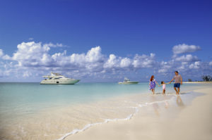 Mom, dad and young daughter walking on the beach with motor boats in the back ground