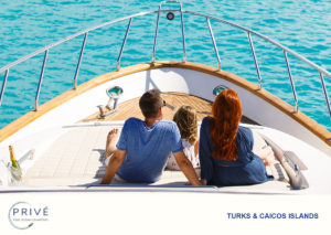 Family gazing out over the bow of yacht with deserted island and beach in the distance