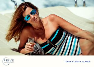 Woman in one-piece swimsuit and sunglasses reclining on elbow with glass of champagne on the bow of a luxury motor yacht