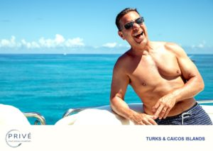 Shirtless man in swimsuit on the bow of a luxury sports yacht laughing