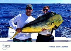 Captain Trish and shirtless guest proudly displaying Mahi Mahi catch