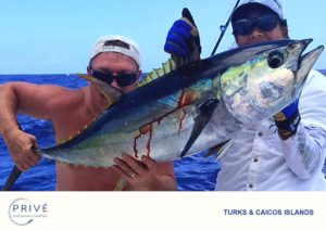 Captain Trish and shirtless guest proudly displaying yellow fin tuna catch