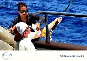 Captain Trish assisting a young angler as he fights to reel in his catch