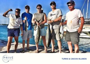 four anglers posing with boat captain showing off their tuna catch