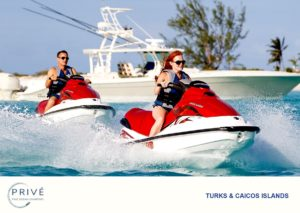 Man and woman riding jet skis with motor boat in the background