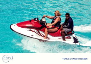 Yacht crew member riding along with guest of jet ski