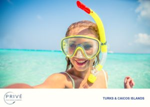 Attractive young woman taking a selfie with her mask and snorkel gear on with a sunny turquoise blue sky and horizon in the background