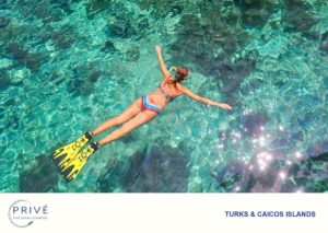 View of woman snorkeler floating on top of the turquoise water face down