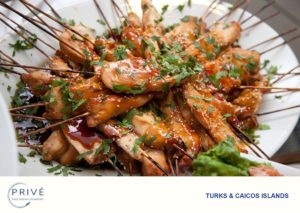 Plate of Asian chicken satay skewers garnished with chiffonade of cilantro