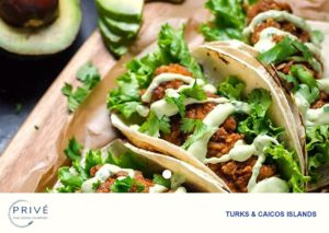 Fried chicken filled tacos garnished with cilantro and garlic aioli