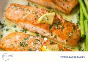 Several pan seared and baked salmon fillets, with fresh herbs and asparagus