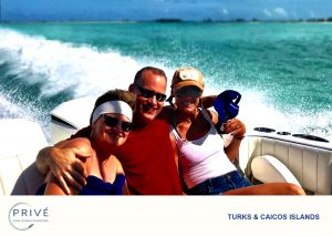 Trio on the back of motor boat, man in the middle hugging two women