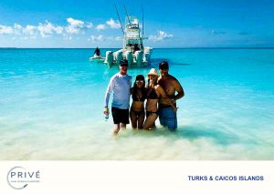 Two couples posing in the shallows with boat charter in the background
