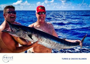 Two guests holding fresh Wahoo catch with big winning-grins