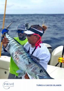 Man and woman holding a 5' wahoo fish