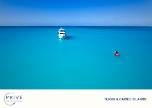 Ariel photo of jet ski rider and yacht surrounded by blue water and skis