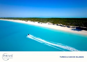 Solitary jet ski riding alongside white sand beach in turquoise blue water
