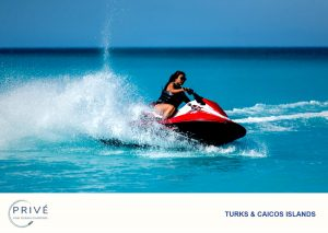 Woman with sunglasses on red jet ski in turquoise blue water