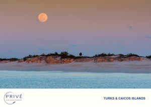 Rising full moon contrasted against pastel cotton candy skis over a deserted island